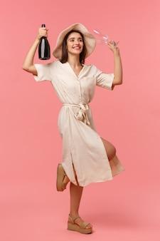 Портрет счастливой харизматичной молодой девушки в шляпе и платье, танцующей с поднятой бутылкой шампанского