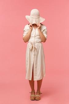 夏の後ろに彼女の顔を隠してドレスに立っている愚かな恥ずかしがり屋の女の子の全身縦型ポートレート