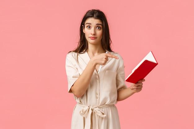 あなたはこれを書きましたかノートに書かれた何かについて質問する興味をそそるブルネットの少女