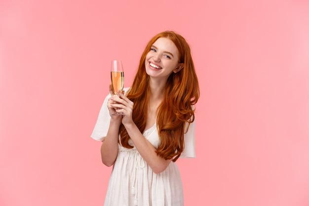 Беззаботная, возбужденная милая рыжая женщина празднует день рождения, посещает модные вечеринки, надевает белое платье
