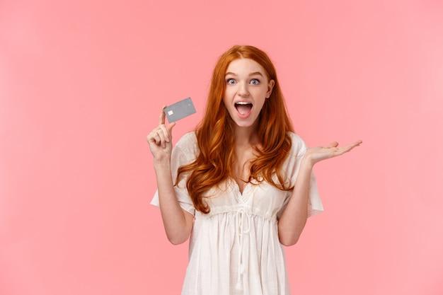 Удивленная и впечатленная милая счастливая, веселая рыжая женщина поражена тем, что получила потрясающие бонусы
