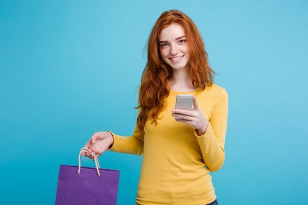 ショッピングコンセプト - クローズアップ肖像画若い美しい魅力的な赤毛の女の子ショッピングバッグでカメラを見て笑って。青いパステルの背景。スペースをコピーします。
