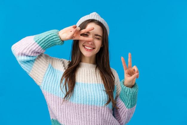 Собирай вещи и путешествуй. радостная и беззаботная жизнерадостная улыбающаяся женщина, надевайте зимний свитер