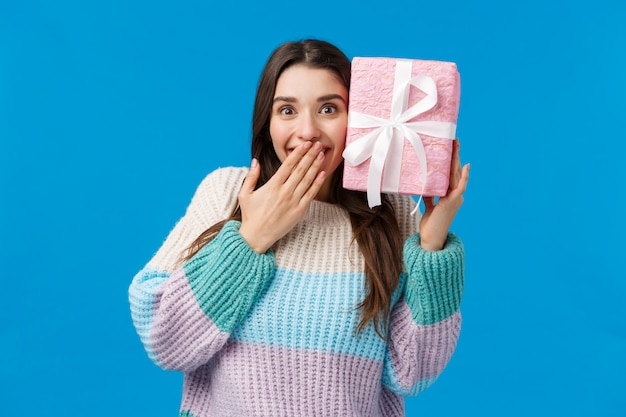 Счастливая жизнерадостная милая женщина угадывает, что внутри коробки, получила настоящий улыбающийся изумленный