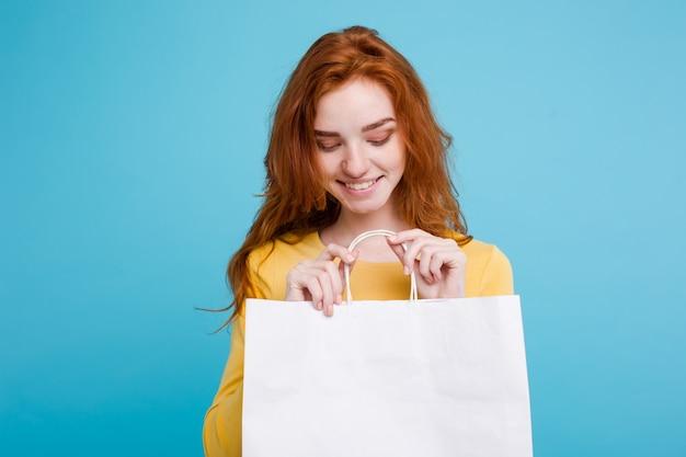ショッピングコンセプト - クローズアップ肖像画の若い美しい魅力的な赤毛の女の子は、白いショッピングバッグでカメラを見て笑顔。青いパステルの背景。スペースをコピーします。