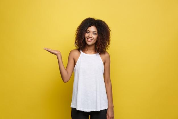 美しい魅力的なアフリカ系アメリカ人の女性は、彼女の縮毛アフロの髪を再生する投稿します。黄色のスタジオの背景。スペースをコピーします。