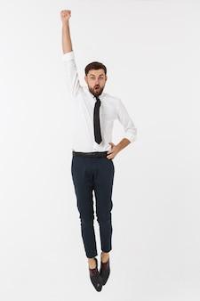 Молодой счастливый кавказский бизнесмен скача в воздух, изолированный на белизне.