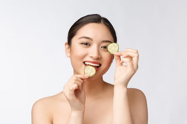 自然な自家製の新鮮なキュウリの顔のアイパッドフェイシャルマスクキュウリのパッドを保持しているアジアの女性と笑顔は自然な自家製でリラックス
