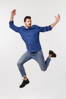 Привлекательный спортивный бизнесмен прыгает против