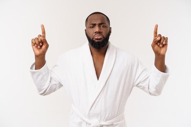 驚きと幸せな感情白で分離されたバスローブ人差し指を着ているアフリカ系アメリカ人の男