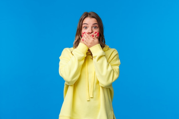 Потрясенная и безмолвная, впечатленная белокурая женщина закрывает рот руками и удивленно смотрит, слышит потрясенный слух, сплетни делают изумленное лицо,