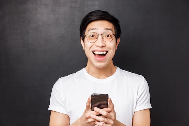 興奮して面白がって幸せなアジア人のクローズアップの肖像画
