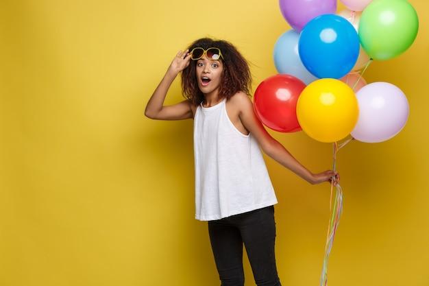 Празднование концепции - закрыть портрет счастливый молодых красивых африканских женщина в черной футболке, улыбаясь с красочный участник воздушного шара. желтая пастельная студия фон.
