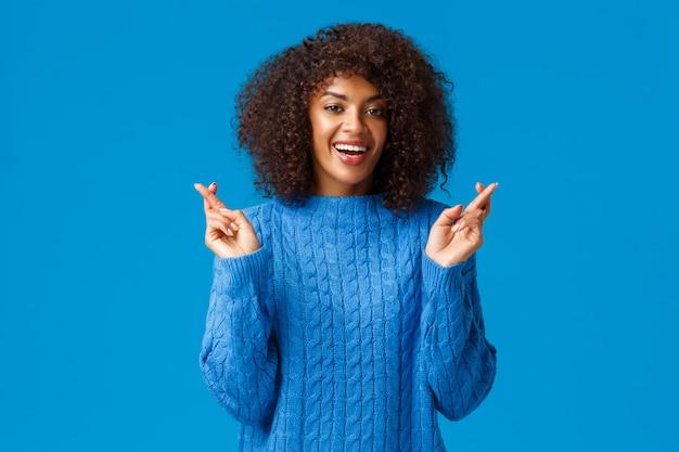私の新年の願いが叶うことを願っています。陽気で希望に満ちた、楽観的な冬のセーターの美しいアフリカ系アメリカ人女性、幸運と興奮して笑顔のために指をクロス、夢の実現を期待