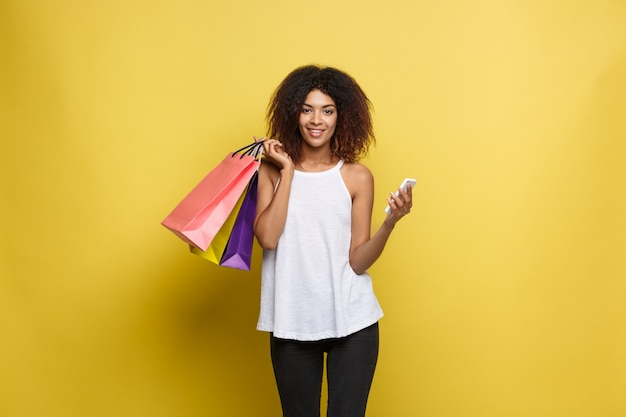 ショッピングコンセプト - クローズアップ肖像画若い美しい魅力的なアフリカの女性は、笑顔とカラフルなショッピングバッグで楽しい。黄色のパステルの壁の背景。スペースをコピーします。