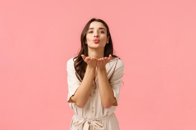 Посылаю любовь и заботу. очаровательная милая и нежная европейская брюнетка с вьющимися волосами, в весеннем платье, опираясь руками на сложенные губы, дует воздушный поцелуй с любовью, стоящая розовая стена