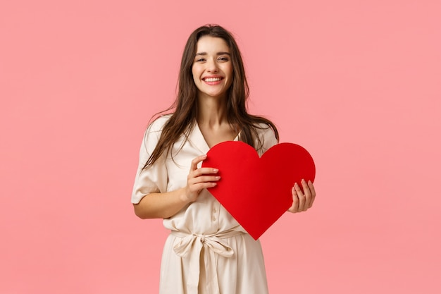 愚かな、のんきな、素敵な魅力的なデザインの凝った服のブルネットの少女、赤い大きなハートのカードを持っている、これまでで最高のバレンタインデーを持っている、笑顔で笑って喜んでいる、明るいピンクの壁に立っている