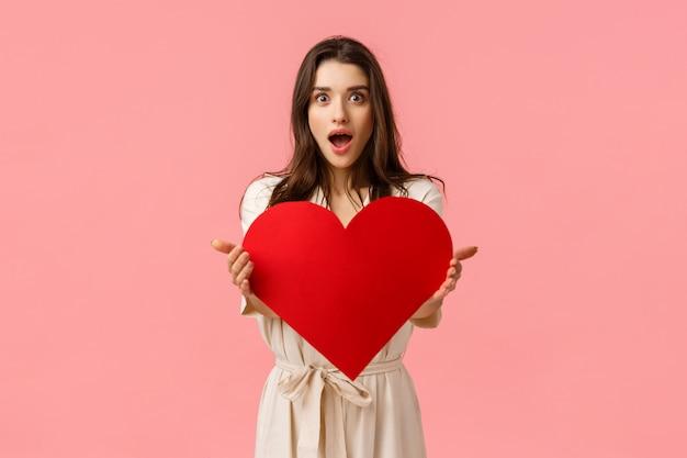 驚き、贈り物、関係概念。愛を送信し、愛情を示し、赤いハートのカードを保持し、バレンタインの日を与え、ピンクの壁に立っている魅力的な優しくてフェミニンな魅力的な女の子