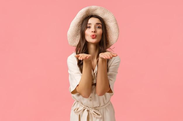 Нежность, гламур и романтика концепции. элегантная, симпатичная, женственная женщина в шляпе и платье, складывая губы, глупо дует воздушный поцелуй и посылает вам ладони, дарить любовь, розовая стена