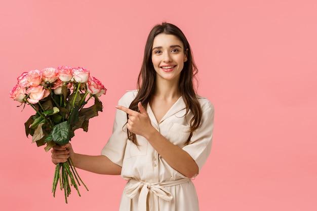 プレゼント、バレンタインデー、美容コンセプト。ゴージャスなフェミニンな女の子の花屋は、顧客のために美しい花束を作り、バラを持って花に指を向け、愚かな、幸せなピンクの壁を笑顔