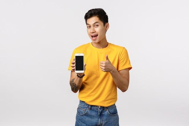 Привлекательный азиатский парень в желтой стильной футболке с татуировками, показывает палец вверх и дисплей телефона, предлагая клиенту загрузить удивительное приложение, приложение для редактирования, игру или корпоративную страницу