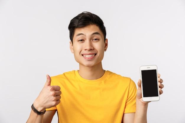 Жизнерадостный крупный план, дружелюбный азиатский мужчина в желтой футболке, большой палец в знак одобрения, как жест, показ на дисплее телефона, продвижение интернет-сайта, корпоративный баннер или профиль в социальной сети, белая стена