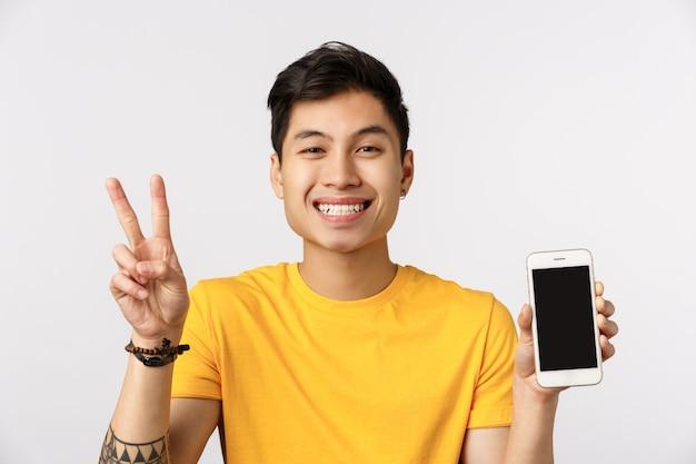 Крупным планом привлекательный восторженный, радостный азиатский мужчина в желтой футболке, показывающий знак мира и экран телефона, рекламирующий приложение, мессенджер или приложение для каршеринга, белая стена