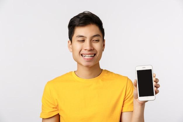 Смешной и красивый эмоциональный современный молодой азиатский человек продвигает приложение, показывая телефонное устройство, смотрит на экран и смеется, улыбается довольный, стоит белая стена рекомендует устройство