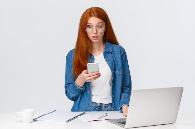 Потрясенная и потерявшая дар речи удивленная рыжая женщина смотрит на дисплей телефона, читает захватывающее шокирующее сообщение, стоит возле рабочего стола, ноутбука, белой стены