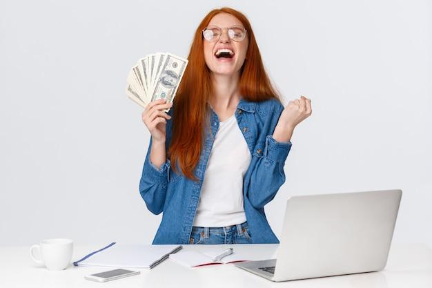 Облегченная и счастливая девушка становится богатой после того, как она много делает, пожимает руки, нажимает на кулак да и поднимает голову в небо в восторге, держит большие деньги, деньги рядом с дест с ноутбуком, белая стена