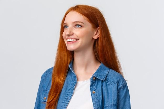 クローズアップの肖像画の美しい景色を見て夢のようなかわいい明るい赤毛の女性、素晴らしい何かを熟考し、笑みを浮かべて、左上隅を見て喜んで、白い壁