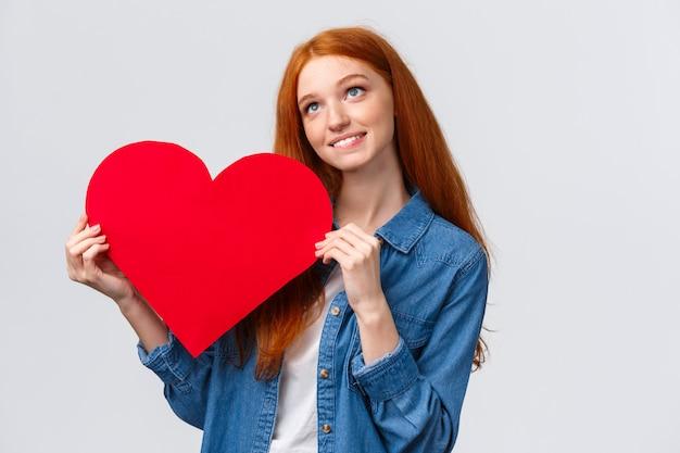 夢のような素敵な白人赤毛の女性は恋人にバレンタインの日カードを与えることを夢見て、思慮深い、イメージングシーンを探して、大きな赤いハートを持って、幸せそうに笑って、白い壁