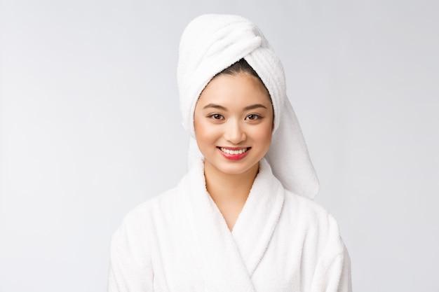 Спа по уходу за кожей красоты азиатская женщина сушки волос полотенцем на голове после душа. красивая многорасовых молодая девушка, касаясь мягкой кожи.