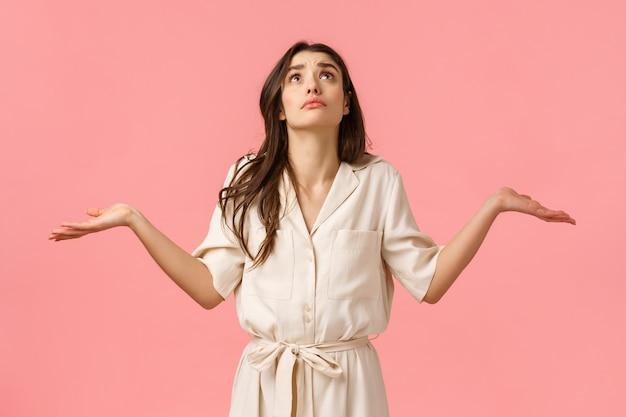 女の子は信仰が準備したものを理解できません。混乱し、優柔不断な魅力の若いブルネットの少女のドレス、横に手を肩をすくめて、ふくれっ面の雨、ピンクの壁を見上げる