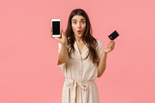 ショッピングディスカウントイベント中にガールフレンドが銀行口座のすべてのお金を浪費し、クレジットカードの折りたたみ唇をばかげて保持し、スマートフォンの画面を表示し、驚いたピンクの壁に立っている