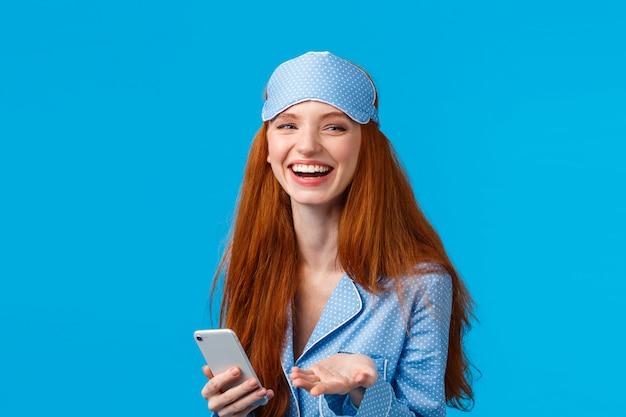 ナイトウェア、パジャマ、スリープマスクで幸せでカリスマ的な素敵な赤毛の女性、笑って、かわいい笑顔を言って、スマートフォンを話すルームメイトを押し、青い壁に立っています。