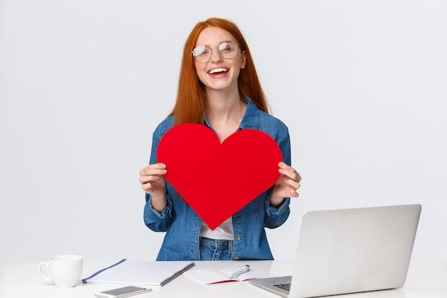 バレンタインデー、創造性と感情の概念。陽気な笑顔の赤毛の女の子、長距離の関係でインターネットを介して彼女の愛を送り、ウェブカメラを使用して大きな赤いハートを見せ、あなたを愛していると言う