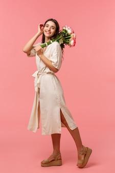 フルレングスの縦長の肖像画、デートを楽しむ夢のようなロマンチックなブルネットの女性、花束のバラを保持、優しく髪に触れる、愚かな笑顔、花を受け取る、立っているピンクの壁
