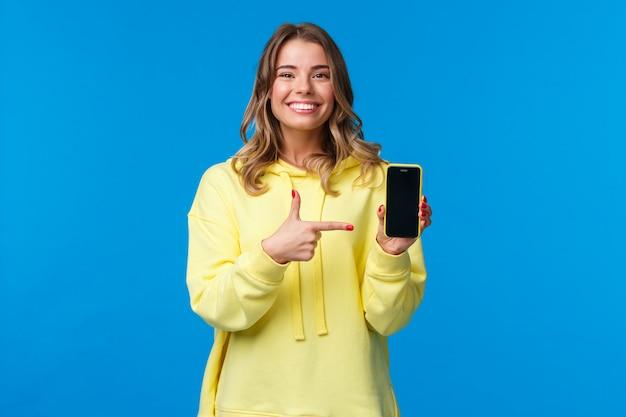 誇りに思っている陽気な若いブロンドの女性は、新しいモバイルゲームまたはアプリケーションを宣伝し、カメラを見て、スマートフォンのディスプレイを指しているように白い歯を笑顔にして、ダウンロードを推奨するか、試してみる