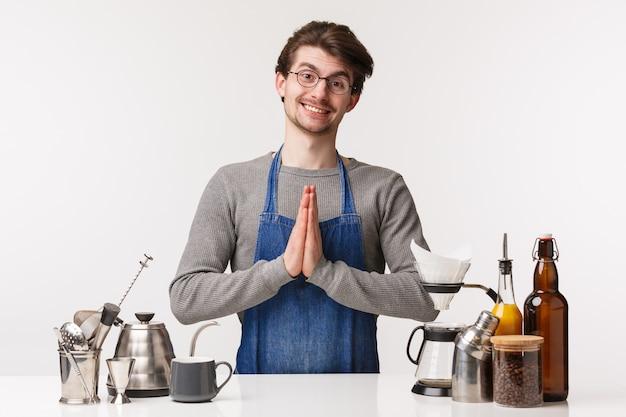 バリスタ、カフェワーカー、バーテンダーのコンセプト。祈りの中で手を繋いでいるエプロンで希望に満ちた天使のような若い男は、クライアントの願いを叶える準備ができて、エプロンで働く愚かな笑顔のコーヒーを作る