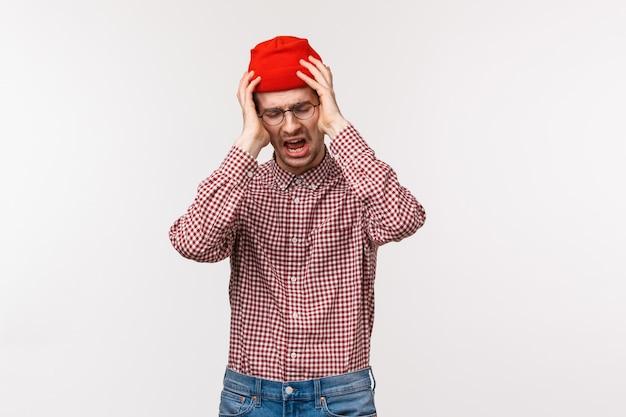 絶望的な悲惨で悲しい耳が痛い男が頭を掴んで動揺し、大きなひどい問題に直面している、彼がしたことをどのように修正するのかわからない、不安で立っている