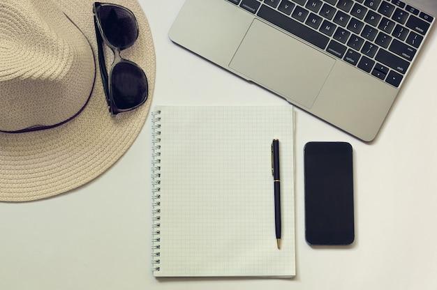 ブロガー、作家、またはフリーランサーの職場で、ラップトップ、ノートブック、電話、ペン、帽子。
