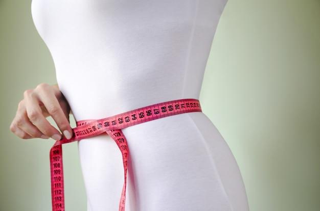 測定テープと白い下着の細い女の子のウエスト