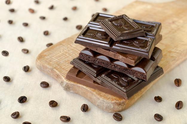 Грубые кусочки шоколада на деревянной доске, кофейные зерна разбросаны по всему