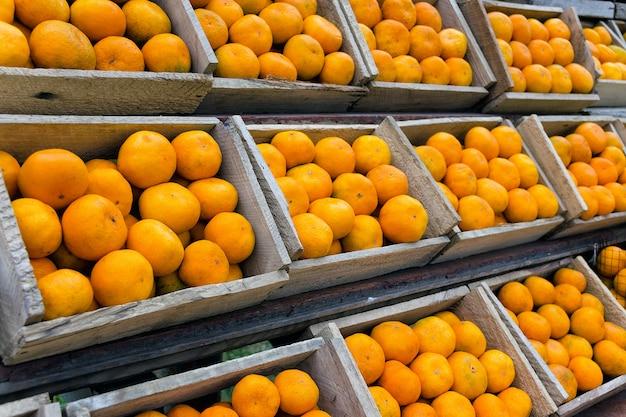 Ряды деревянных ящиков с спелых мандаринов.