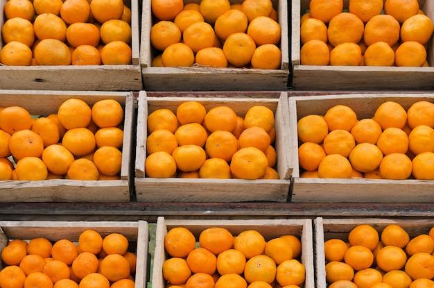Спелые мандарины в деревянных ящиках стоят в ряд.