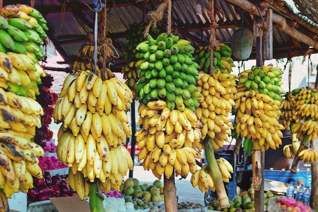 Фруктовый магазин на улице шри-ланки с разнообразными продуктами и большими ветвями с бананами. сельскохозяйственная продукция в азии.
