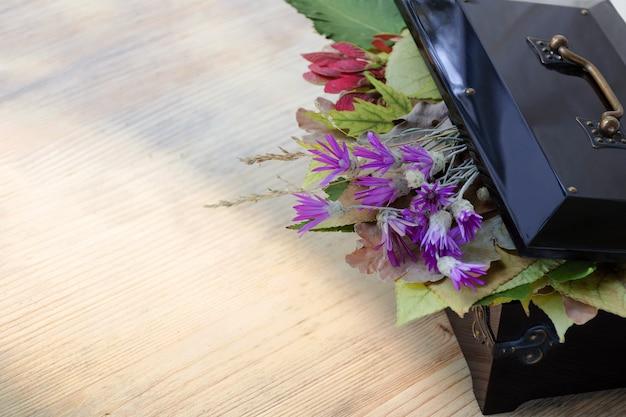 秋の葉と野生の花の中でビンテージボックス。