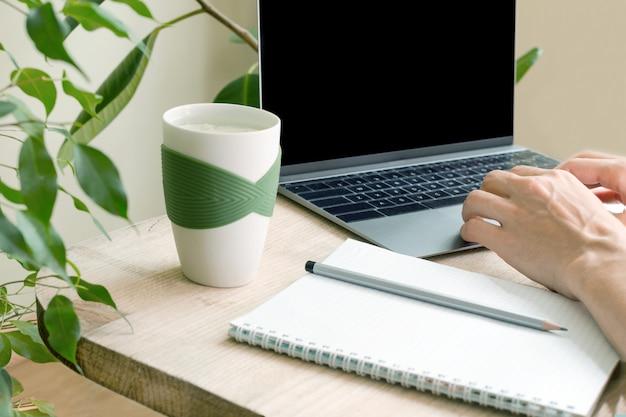 ノートパソコンのキーボードの手。緑の植物に囲まれたアパートの職場。