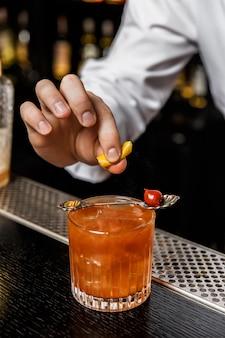 バーでカクテルを事前に準備し、ロックグラスでドリンクの上にレモンの皮を絞るバーテンダー